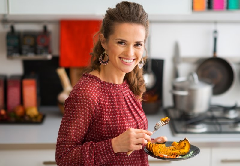 Smiling woman with Thanksgiving meal on plate