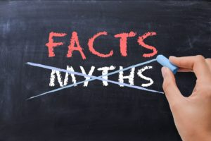 Chalkboard illustrating difference between facts and dental implant myths